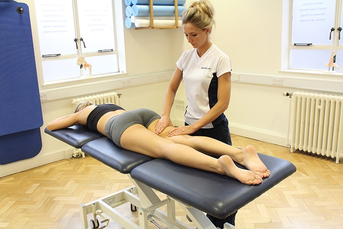 Kneading massage technique used on upper thigh of customer in Manchester clinic