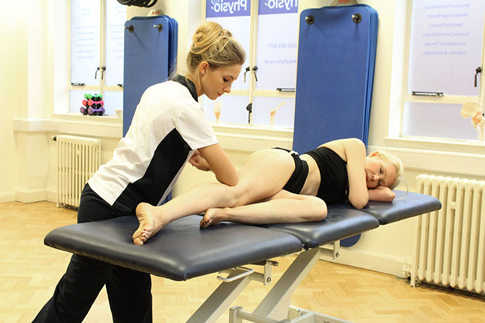 Sports massage treatment on upper leg in Manchester clinic