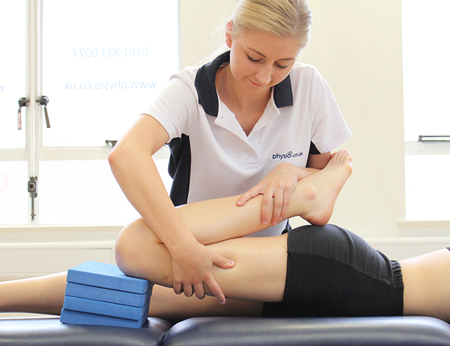 Female physiotherapist treats leg injury on patient.