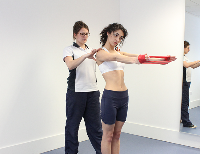 Experienced physiotherapist instructs patient how to carry out exercise.