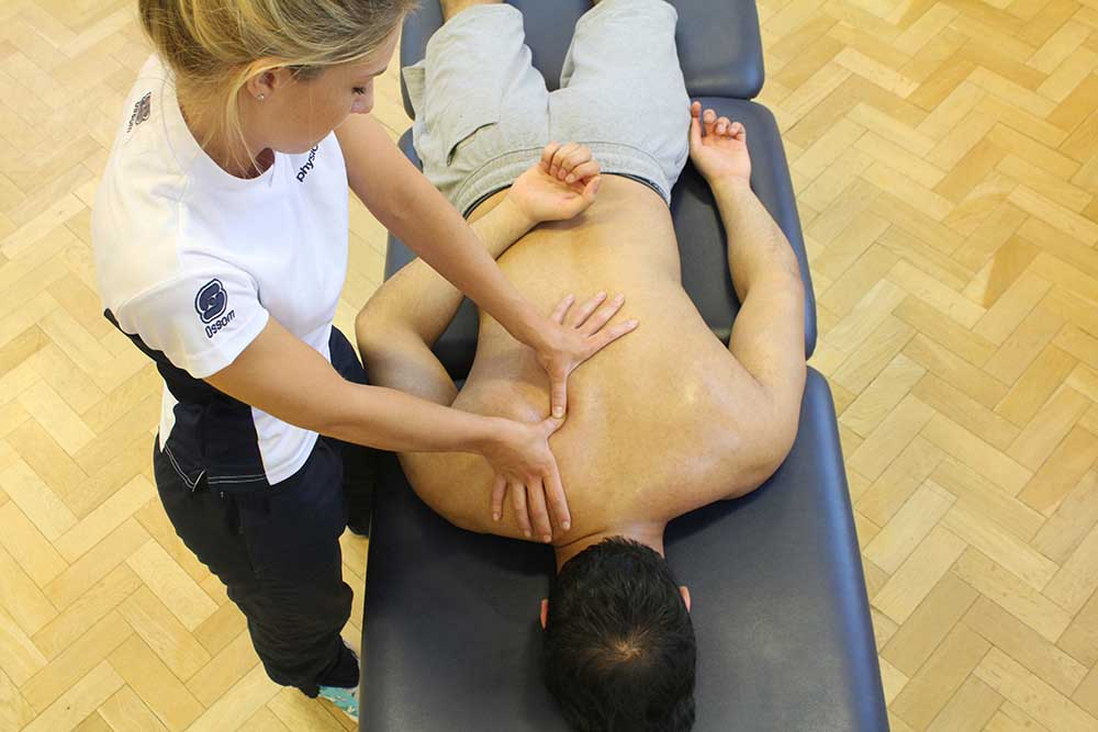 Trigger point massage of the rhomboid muscle by an experienced therapist