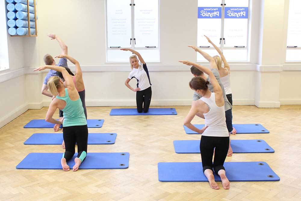 Group pilates session warm up on mats.