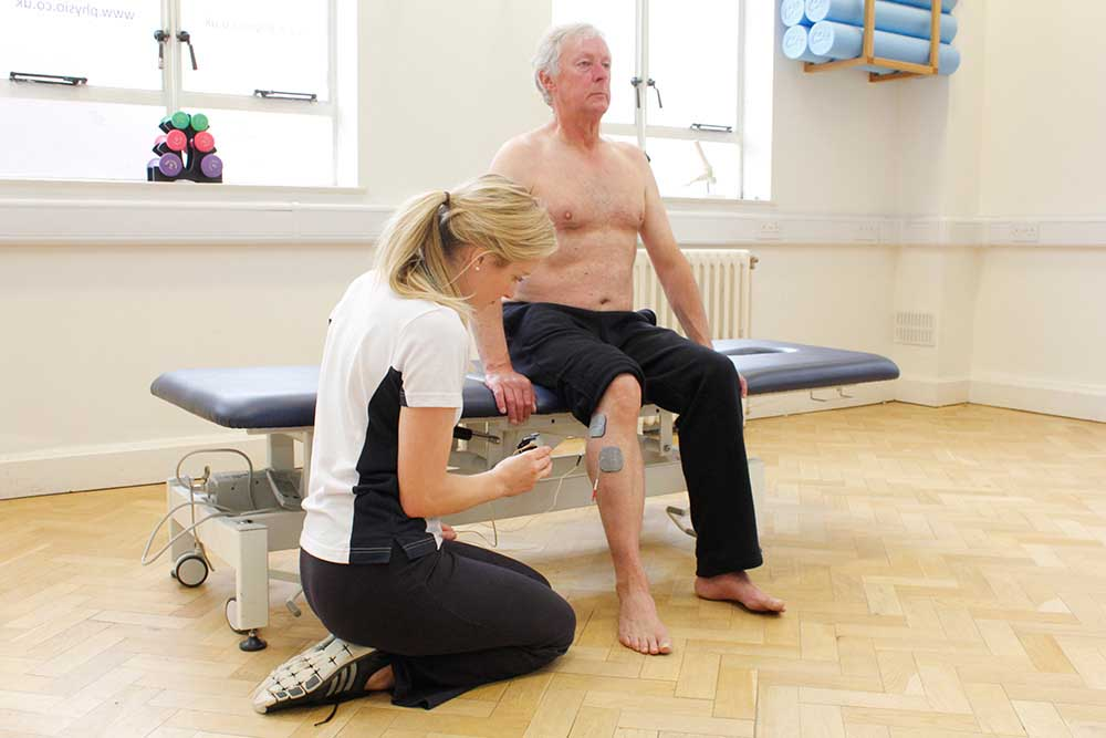Neurological physiotherapist applying functional electrical stimulaltion treatment to aid mobility