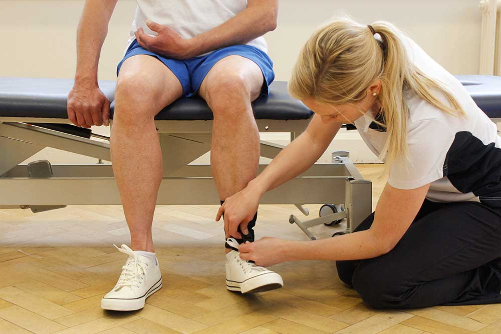 Physiotherapist fitting an ankle orthotic to limit foot drop and prevent trips and falls
