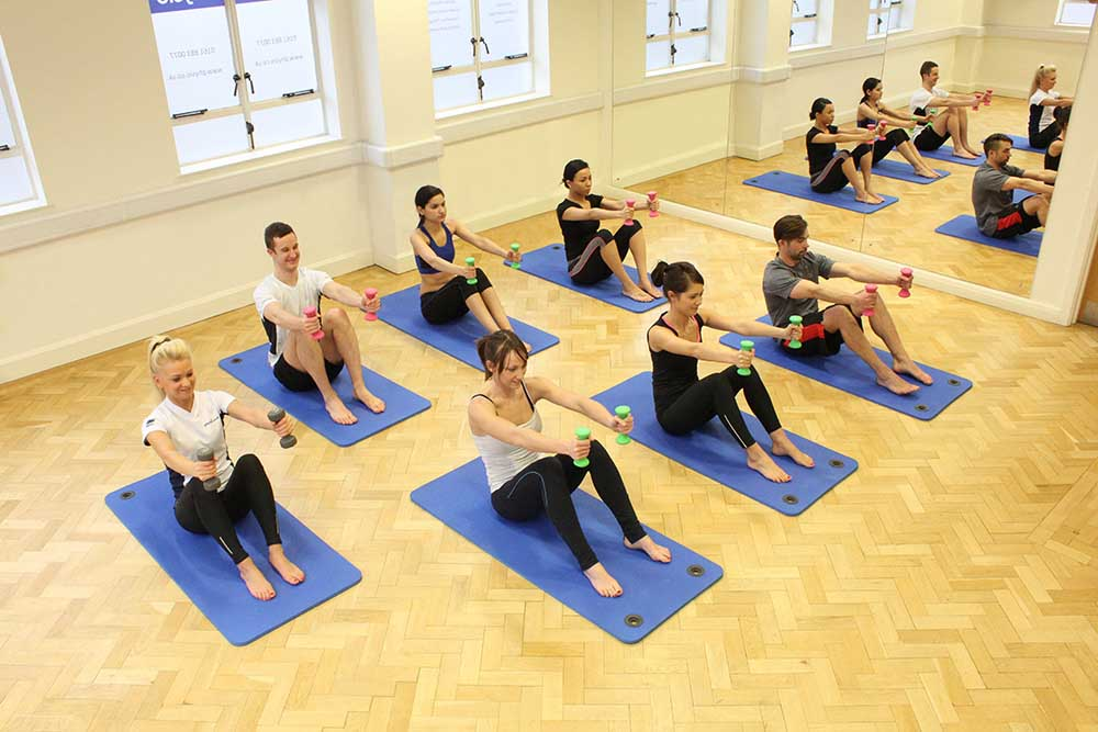 Physiotherapist led pilates class using small weights