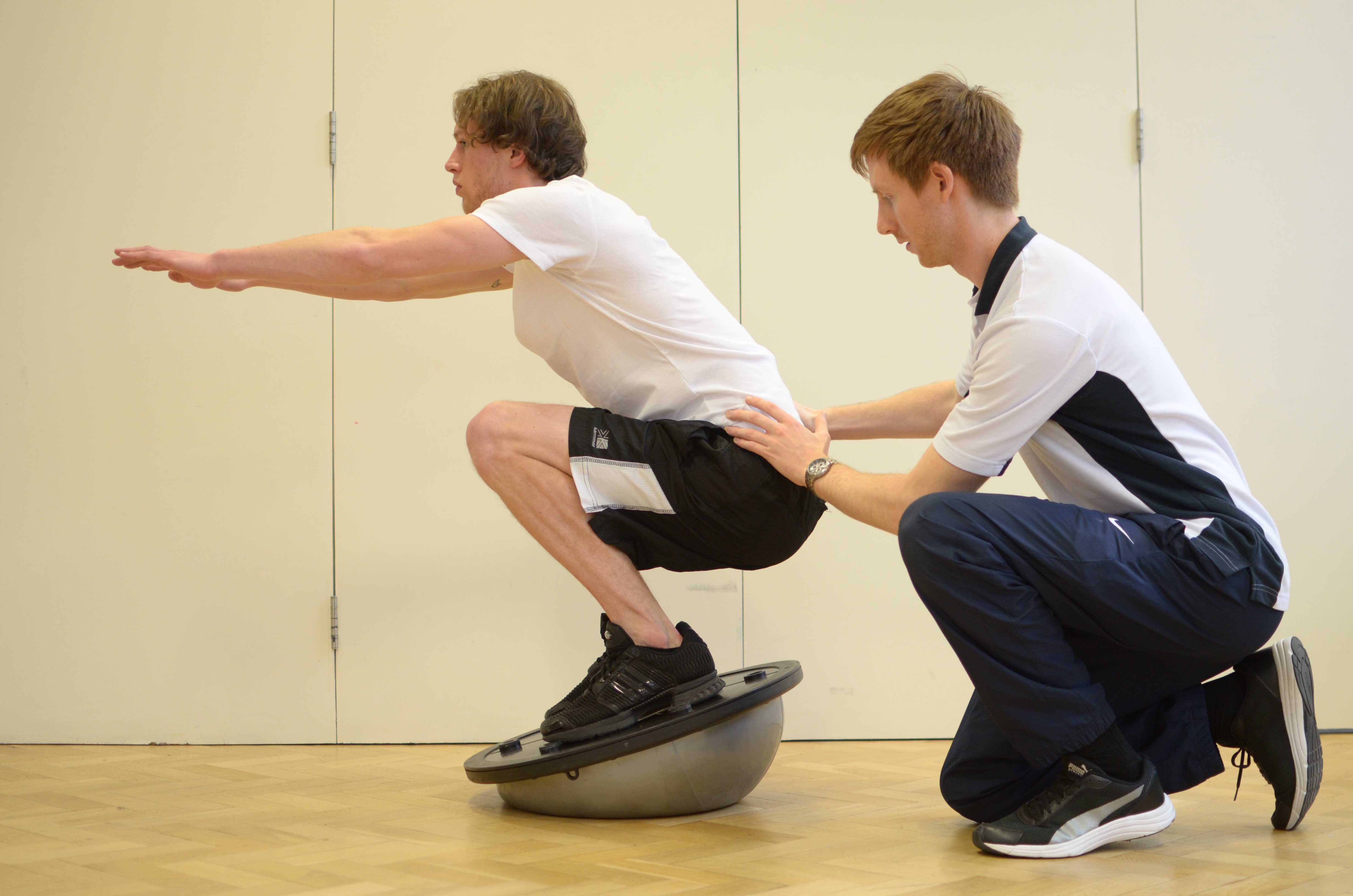 Leg strengthening and stability exercises using squats on a balance board under supervision of specialist MSK physiotherapist