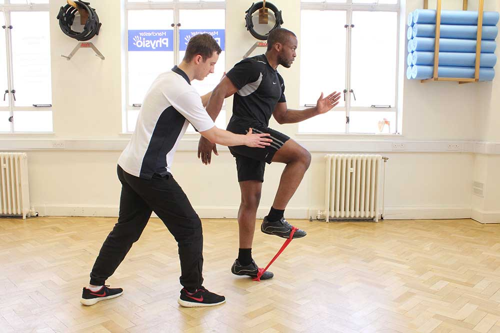 Physiotherapist supervising lower limb exercises using a resistance band.