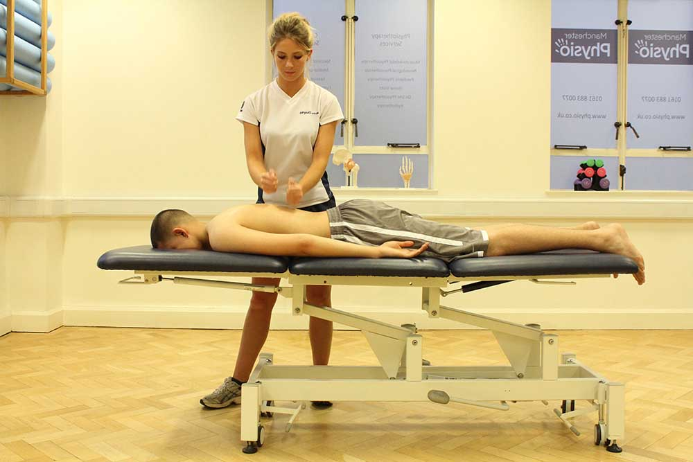 Sports massage focused on latissimus dorsi muscle using percussion technique